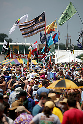 29 April 2012. New Orleans, Louisiana,  USA. <br /> New Orleans Jazz and Heritage Festival. <br /> Hundreds of flags fill the air, helping friends locate friends in the massive crowd on hand to see Bruce Springsteen. <br /> Photo credit; Charlie Varley/varleypix.com