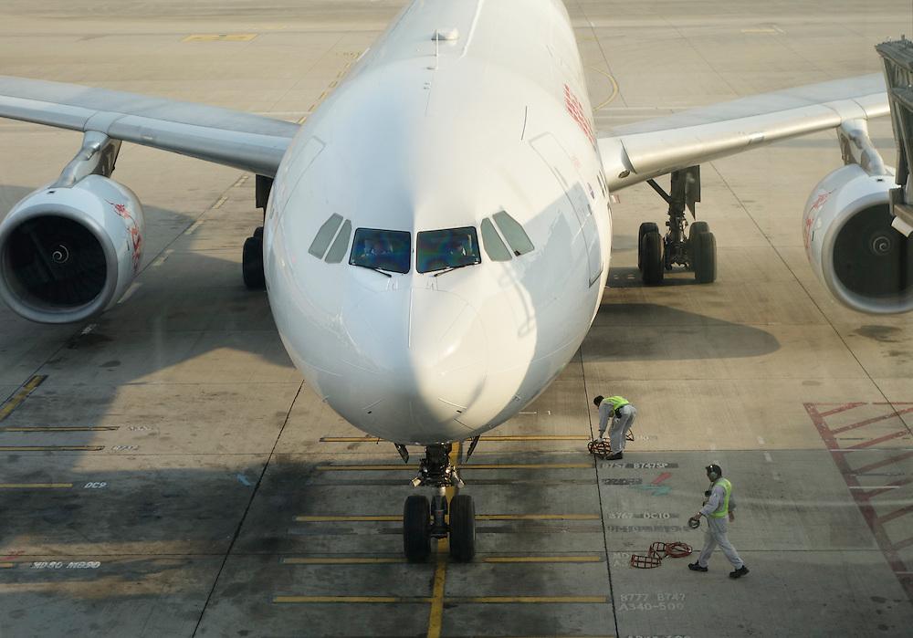 Passenger jet arriving at a gate at Hong Kong International Airport, China.