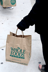 June 16, 2017 - New York, New York, U.S. - A customer holds Whole Foods bags after purchasing groceries outside the Upper East Side 87th Street Whole Foods location. Amazon announced it planned to purchase Whole Foods for $13.4 billion. (Credit Image: © Nancy Kaszerman via ZUMA Wire)