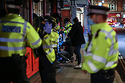 Police stop and search two people as others continued to drink outside a bar in Soho, London on Friday, Oct 9, 2020 -  after the 10 pm curfew. Pubs and restaurants are subject to in order to curb the spread of coronavirus. Boris Johnson is to outline a new three-tiered system of coronavirus restrictions on Monday that is expected to cause pubs and restaurants to shut across the north of England.<br /> (VXP Photo/ Vudi Xhymshiti)