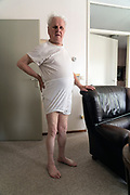 portrait of an 90+ year senior man in his underwear standing