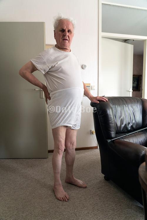 portrait of an 90+ year senior man in his underwear standing