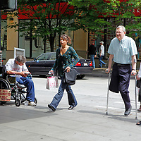 Two One-Legged Men in very different states of coping - one is in a wheelchair with a sign needing money, the other crosses the street with crutches and a woman who is spending money.