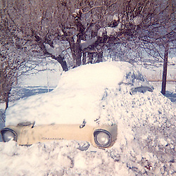 Snow covered 57 Chevy taken in 1973 in Utah. 57 Chevy is yellow in color.