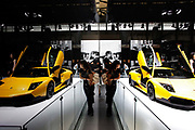 A woman has her pictures taken with Lamborghini sports cars on display at the Auto Shanghai 2009 in Shanghai, China on 20 April 2009.  China's automobile market saw a rapid growth in the past decade and it is now the biggest automobile market in the world, the title has come with a price however, with many cities roads clogged, some local governments are issuing new directives limiting new vehicle purchases.