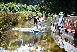 © Licensed to London News Pictures. 04/09/2021. Brecon, UK. A stand-up paddle boarder makes his way down the Monmouthshire and Brecon Canal in South Wales on a beautiful Saturday afternoon as people enjoy the late Summer weather across the UK. Photo credit: Robert Melen/LNP