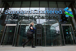 © licensed to London News Pictures. London, UK 07/08/2012. People walking past Standard Chartered's HQ in London on 07/08/12. Standard Chartered bank has been accused of hiding $250bn worth of illegal transactions with Iranian banks over nearly a decade. Photo credit: Tolga Akmen/LNP