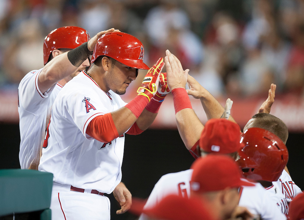 The Angels' Carlos Perez celebrates with teammates after hitting a sac fly to score Johnny Giavotella during a five run fifth inning against the Dodgers Wednesday night at Angel Stadium.<br /> <br /> ///ADDITIONAL INFO:   <br /> <br /> angels.0519.kjs  ---  Photo by KEVIN SULLIVAN / Orange County Register  -- 5/18/16<br /> <br /> The Los Angeles Angels take on the Los Angeles Dodgers in inter-league play at Angel Stadium Wednesday night.
