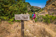Trail sign and hiker at Lobo Canyon, Santa Rosa Island, Channel Islands National Park, California USA