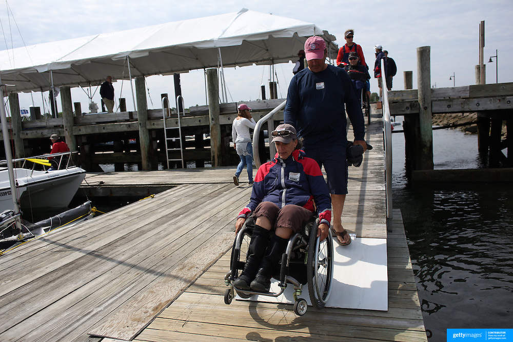 Skipper Sarah Everhart Skeels, Tiverton, RI, arrives on the dock in her wheelchair before sailing with  Cindy Walker, Middletown, RI, the only all female team competing in The Skud 18 class, during the C. Thomas Clagett, Jr. Memorial Clinic & Regatta at Newport, Rhode Island hosted by Sail Newport at Fort Adams. <br /> The Clagett is North America's premier event for sailors with disabilities with sailors competing in the 3 Paralympic class boats and is an integral part of preparation for athletes preparing for  Paralympic and world championship racing. Newport, Rhode Island, USA. 26th June 2015. Photo Tim Clayton