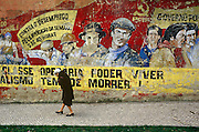 Old Communist graffiti adorns the walls of a crumbling building as an elderly lady walks past.