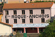 Etablissement Roque Anchois anchovies factory, house painted with advertising in black and pink. Collioure. Roussillon. France. Europe.