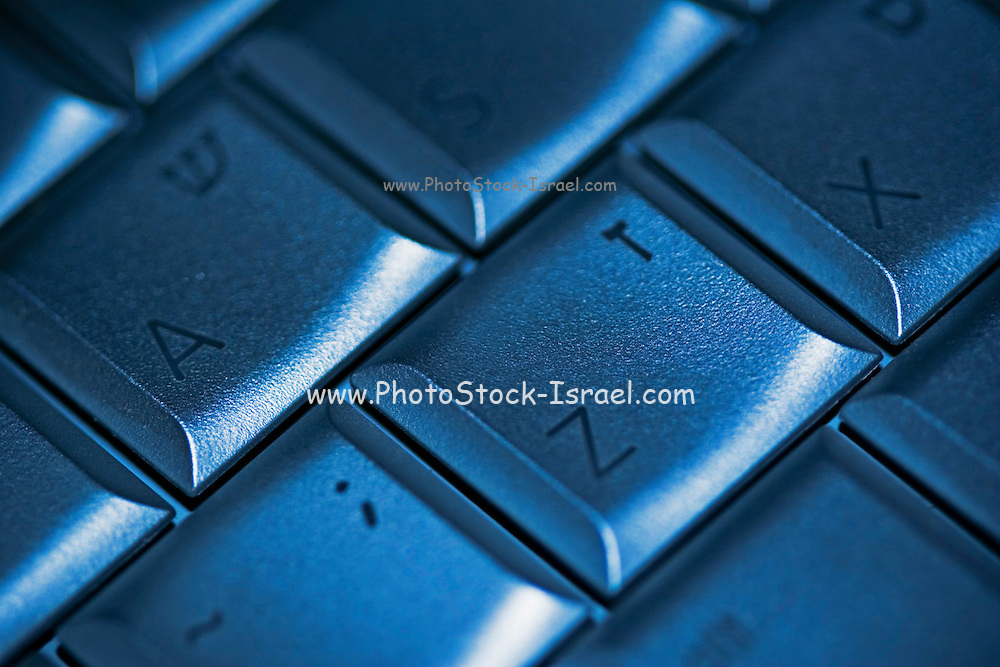 From A to Z computer keyboard with letters in English and in Hebrew on the keys in metallic blue selective focus