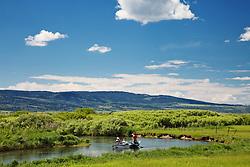 Fly-fishermen floating the Teton River in a drift boat it Teton Valley Idaho