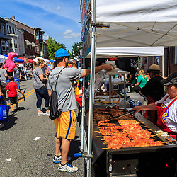 Mechanicsburg, PA, USA - June 21, 2018: A vendor prepares chicken on a stick at the Jubilee Day, the largest, longest running, one-day street fair on the East Coast.