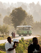 A local bus and people on a road towards Ruhengeri in Parc National Des Volcans, Rwanda