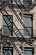 Fire escape ladders and century old apartment building built in stone, in Manhattan, New York City.