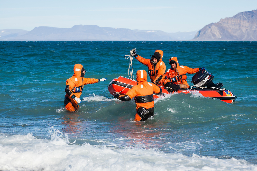 Researchers, dressed in survival suits, navigate an inflatable boat through rough water and back onto shore at the Polish field station in Calypsobyen, Svalbard.