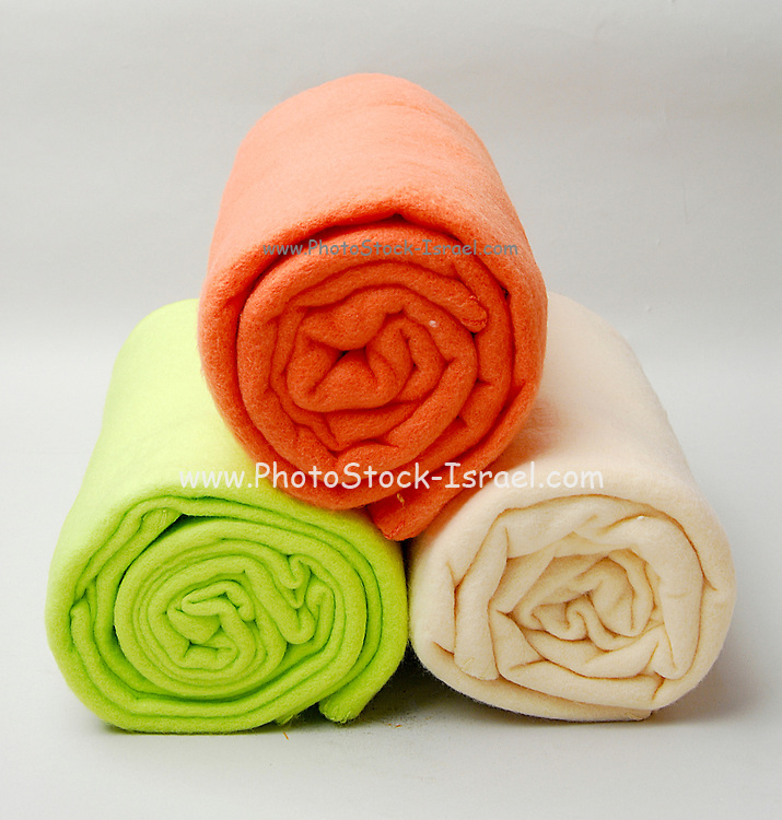 three rolled up towels orange green and white on a white background