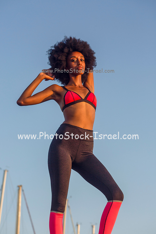 Young athletic woman in sports clothes stretching with a blue sky background