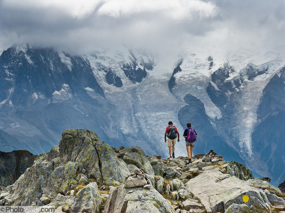 """Day hikers walk the High Route (Chamonix-Zermatt Haute Route) across from vast glaciers of the Mont Blanc Massif, Chamonix, France, Europe, in the Reserve Naturelle Aiguilles Rouges. Published in Ryder-Walker Alpine Adventures """"Inn to Inn Alpine Hiking Adventures"""" Catalog 2006."""