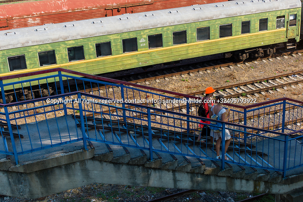 20150826 Bendery, Bender, Transnistria, Moldova.Two young girls walk the stairs at the Bendery-1 trainstation with colorful old trains