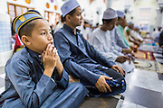 09 JULY 2013 - PATTANI, PATTANI, THAILAND:  A boy prays with his family members in Pattani Central Mosque in Pattani, Thailand, Tuesday night on the first night of Ramadan. Ramadan is the ninth month of the Islamic calendar, and the month in which Muslims believe the Quran was revealed. Muslims believe that the Quran was sent down during this month, thus being prepared for gradual revelation by Jibraeel (Gabriel) to the Prophet Muhammad. The month is spent by Muslims fasting during the daylight hours from dawn to sunset. Fasting during the month of Ramadan is one of the Five Pillars of Islam.   PHOTO BY JACK KURTZ