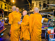 """27 NOVEMBER 2012 - BANGKOK, THAILAND: Buddhist monks on the street in front of Wat Saket during the temple's annual fair. Wat Saket, popularly known as the Golden Mount or """"Phu Khao Thong,"""" is one of the most popular and oldest Buddhist temples in Bangkok. It dates to the Ayutthaya period (roughly 1350-1767 AD) and was renovated extensively when the Siamese fled Ayutthaya and established their new capitol in Bangkok. The temple holds an annual fair in November, the week of the full moon. It's one of the most popular temple fairs in Bangkok. The fair draws people from across Bangkok and spills out in the streets around the temple.    PHOTO BY JACK KURTZ"""