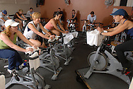 """People burn away calories during a """"Spinning"""" class at a gym."""