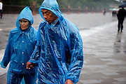 "Couple protected with raincoats during a rainy day the area at ""The Temple of Heaven"" which is a complex of Taoist buildings situated in the southeastern part of central Beijing. Beijing is the capital of the People's Republic of China and one of the most populous cities in the world with a population of 19,612,368 as of 2010."