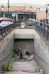 Fly tipped rubbish at entrance to bricked up pedestrian underpass in rundown area awaiting regeneration Dagenham East London UK
