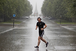 © Licensed to London News Pictures. 07/08/2021. London, UK. A man jogs during heavy rain in Greenwich Park in South East London. A yellow weather warning for thunderstorms is in place for parts of England. Photo credit: George Cracknell Wright/LNP