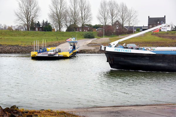 Nederland, the netherlands, Doornenburg, 29-11-2018 Nog nooit stond het water in de Waal en het Pannerdensch kanaal zo laag . Binnenvaartschip varen langs het veer, de pont naar Pannerden .de droogte staat het water in de rijn, ijssel en waal extreem laag . Laagterecord en de laagste officiele stand ooit bij Lobith gemeten. Schepen moeten minder lading innemen om niet te diep te komen . Hierdoor is het drukker in de smallere vaargeul . Door te weinig regenval in het stroomgebied van de rijn is het de waterafvoer extreem weinig .  De Waal is het Nederlandse deel van de Rijn en de belangrijkste vaarroute van en naar Rotterdam en Duitsland . Aftakkingen zijn de minder bevaren Neder Rijn en IJssel. De levering, aanvoer van vracht, lading,grondstoffen, voor fabrieken en brandstof wordt problematisch.Foto: Flip Franssen