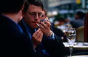 Striking a light in an outdoor café, a young businessman puts a match to his cigarette as a colleague talks in Frankfurt.  Cupping his hand over the lit end, against a shrill wind, the man inhales the nicotine-rich smoke to enjoy another cigarette. On the table in front, an empty glass of German Pilsener, its froth still clinging to the sides of the glass showing that this otherwise healthy gentleman is abusing his body with the addictive tobacco and the thirst-quenching taste of fine beer that has a high percentage of alcohol and rich in carbohydrates. He is smartly dresses, with cufflinks, a good watch and neat hair. In the background are other drinkers and their glasses on tables at this sociable street corner in the city's financial district, a symbolic powerhouse of economic recovery that Germany built in the post-war era.