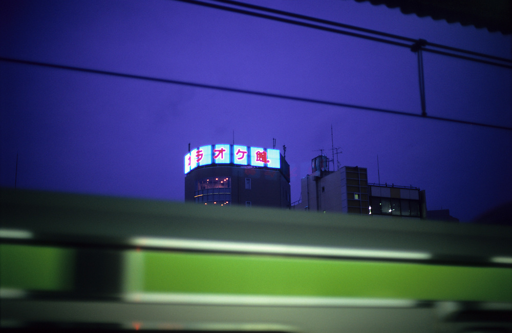 Tokyo train leaving it's station and Karaoke building at night. Japan.