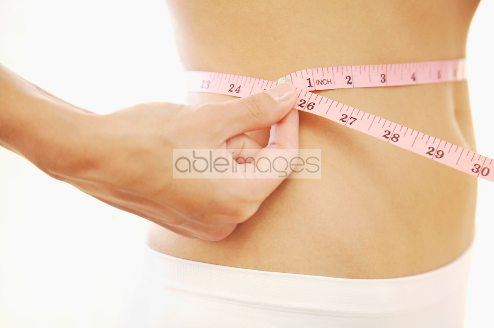 Close up of young woman stomach with measuring tape