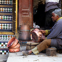 Africa, Morocco, Fes. Worker shaping copper bowls in the souks of Fes.