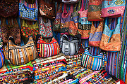 Hand bags and fabric are sold in the Otavalo market, in the Imbabura Province of Ecuador, South America. The culturally vibrant town of Otavalo attracts many tourists to a valley of the Imbabura Province of Ecuador, surrounded by the peaks of Imbabura 4,610m, Cotacachi 4,995m, and Mojanda volcanoes. The indigenous Otavaleños are famous for weaving textiles, usually made of wool, which are sold at the famous Saturday market and smaller markets during the rest of the week. The Plaza del Ponchos and many shops tantalize buyers with a wide array of handicrafts. Nearby villages and towns are also famous for particular crafts: Cotacachi, the center of Ecuador's leather industry, is known for its polished calf skins; and San Antonio specializes in wood carving of statues, picture frames and furniture. Otavaliña women traditionally wear distinctive white embroidered blouses, with flared lace sleeves, and black or dark over skirts, with cream or white under skirts. Long hair is tied back with a 3cm band of woven multi colored material, often matching the band which is wound several times around their waists. They usually have many strings of gold beads around their necks, and matching tightly wound long strings of coral beads around each wrist. Men wear white trousers, and dark blue ponchos. Otavalo is also known for its Inca-influenced traditional music (sometimes known as Andean New Age) and musicians who travel around the world.