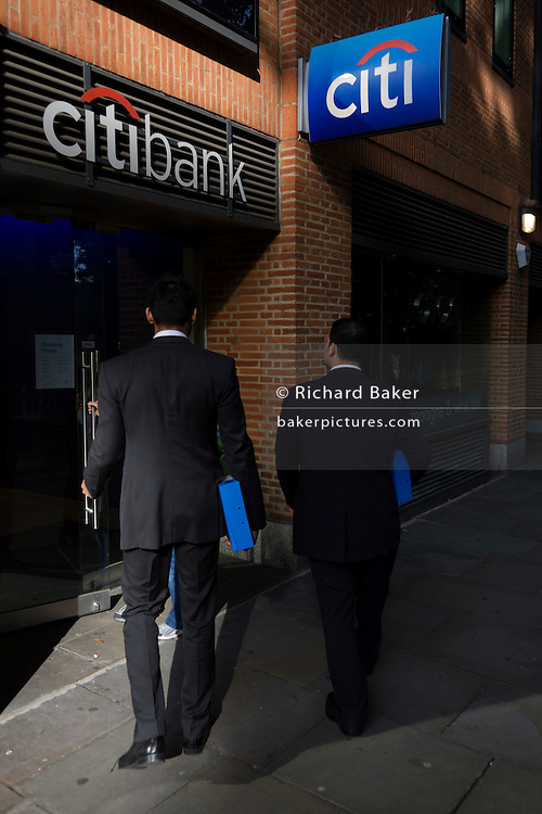 Two businessmen carrying identical blue boxes walk through a London street and enter offices belonging to Citibank.