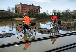 © Licensed to London News Pictures. 03/03/2014. BRISTOL, UK People make their way with bikes through a flooded section of the cycle path and harbour railway line by the river Avon and Cumberland Road in Bristol during this morning's high tide. Photo credit : Artur Lesniak/LNP