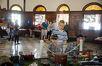 Abraham, Henry and Mark Brogan check out the restored train set on display by Bruce Eisenhauer and Carlton LaSalle inside the Laconia Train Station during the 125th anniversary celebration on Saturday.   (Karen Bobotas/for the Laconia Daily Sun)