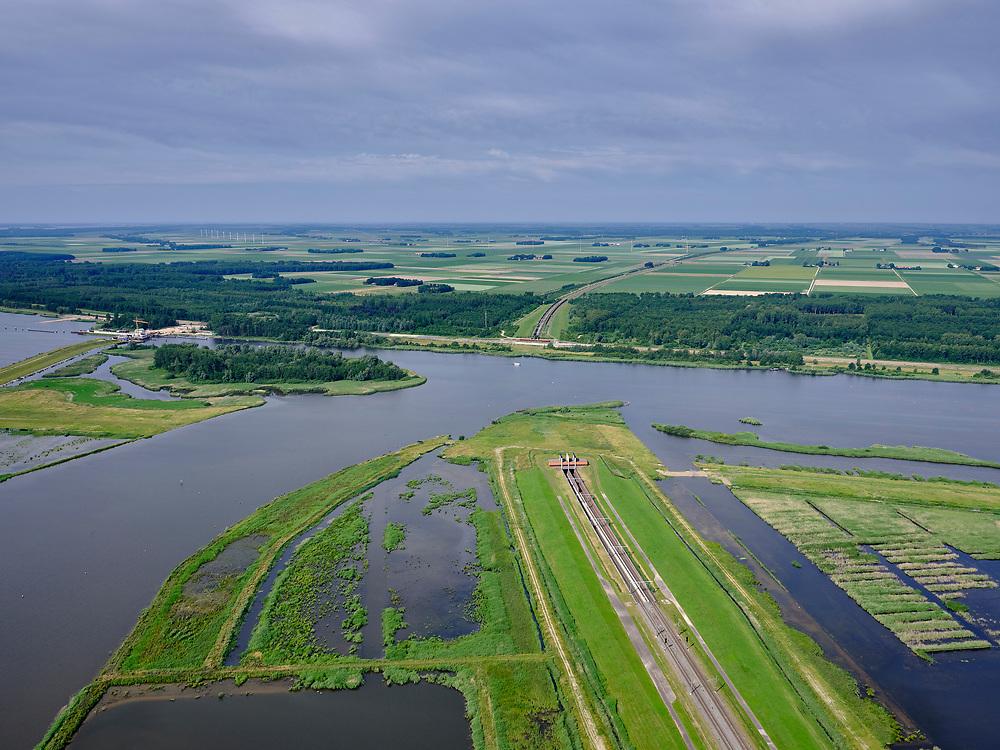 """Nederland, Overijssel, Gemeente Kampen; 21–06-2020; Revemeer (voorheen Drontermeer) met nieuw aangelegd moerasgebied. Ingang tunnel Hanzelijn richting Dronten. Monding Reevediep.<br /> Het Reevediep is aangelegd in het kader van het project Ruimte voor de Rivier om bij hoogwater water af te voeren voordat dit het nabij gelegen Kampen bereikt, direct naar het IJsselmeer, de 'bypass Kampen'. Het Reevediepgebied is ook een natuurgebied en vormt een ecologische verbindingszone tussen rivier de IJssel en Drontermeer.<br /> Revemeer (formerly Drontermeer) with newly constructed wetlands. In the middle to the left the Reevediep in the direction of IJssel.<br /> The Reevediep has been constructed as part of the Room for the River project, and functions to discharge high waters before reaching the nearby Kampen, directly to the IJsselmeer, the """"bypass Kampen"""". The Reevediep area is also a nature reserve and forms an ecological connecting zone between the river IJssel and Drontermeer.<br /> <br /> luchtfoto (toeslag op standard tarieven);<br /> aerial photo (additional fee required)<br /> copyright © 2020 foto/photo Siebe Swart"""
