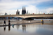 flooding of the Rhine on February 4th. 2021, view from the flooded bank of the Rhine in Deutz to the Deutzer bridge, the Cathedral and the church Gross St. Martin, Cologne, Germany.<br /> <br /> Hochwasser des Rheins am 4. Februar 2021, Blick vom ueberfluteten Rheinufer in Deutz zur Deutzer Bruecke, Dom und Kirche Gross St. Martin, Koeln, Deutschland.