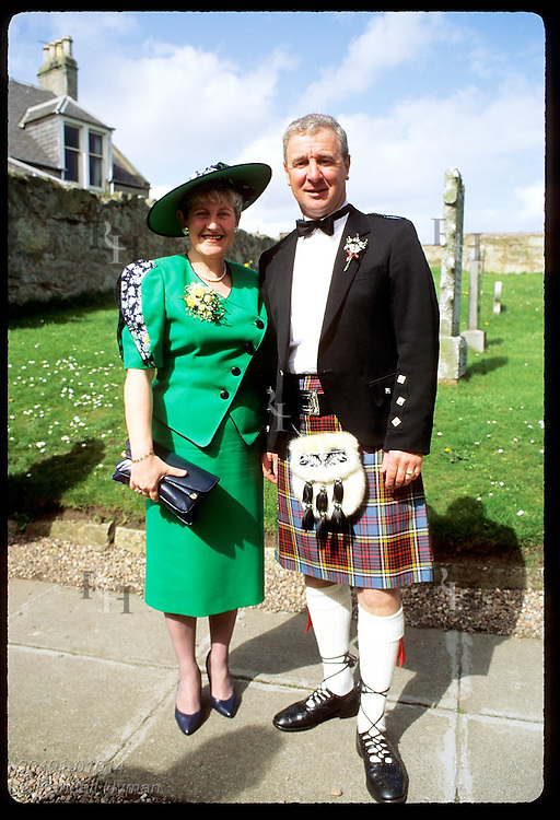 Man in kilt and wife in Easter-green dress pose in churchyard at friend's wedding; Anstruther. Scotland