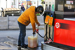 © Licensed to London News Pictures. 29/09/2021. London, UK. A man fills a large container at Texaco petrol station in north London on the sixth day of the fuel crisis, amid fears of fuel running out due to a shortage of HGV drivers. According to the government, 75 army tanker drivers have been put on standby to deliver motor fuel in order to ease the chaos at petrol stations. Photo credit: Dinendra Haria/LNP