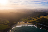 Aerial view of scenic sunset over Purakaunui Bay beach, New Zealand.