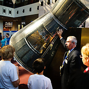 Visitors to the National Air and Space Museum in Washington DC listen to a guide explain the Mercury 7 re-entry vehicle, the capsule that too the first American in space, John Glenn, safely to space and back.
