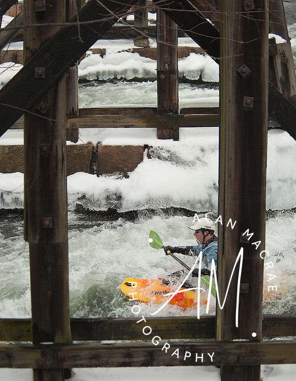 A kayaker makes his way under the Franklin railroad trestle during the 30th annual New Year's Winnipesaukee Kayak run on Saturday, January 1, 2011.  (Alan MacRae/for the Monitor)