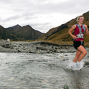 Runner Zoe Dines crosses  Moke Creek on the Ben Lomond High Country Station during the Pure South Shotover Moonlight Mountain Marathon and trail runs. Moke Lake, Queenstown, New Zealand. 4th February 2012. Photo Tim Clayton