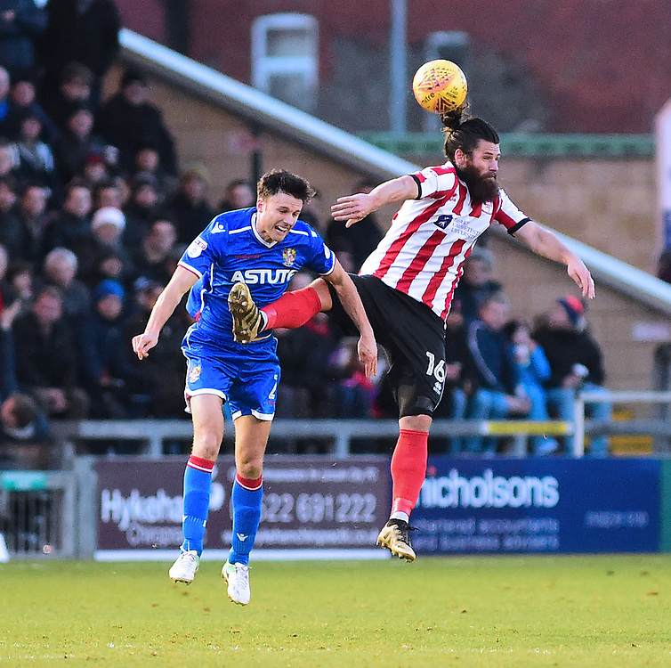 Lincoln City's Michael Bostwick vies for possession with Stevenage's Jonathan Smith<br /> <br /> Photographer Andrew Vaughan/CameraSport<br /> <br /> The EFL Sky Bet League Two - Lincoln City v Stevenage - Tuesday 26th December 2017 - Sincil Bank - Lincoln<br /> <br /> World Copyright © 2017 CameraSport. All rights reserved. 43 Linden Ave. Countesthorpe. Leicester. England. LE8 5PG - Tel: +44 (0) 116 277 4147 - admin@camerasport.com - www.camerasport.com